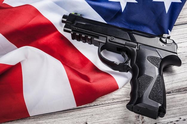 アメリカの国旗の上に横たわる拳銃。武器の問題の概念