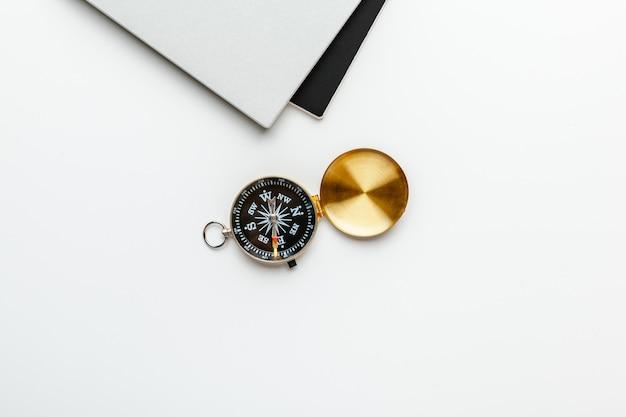 Черный блокнот для морских нот и золотой компас на белом столе