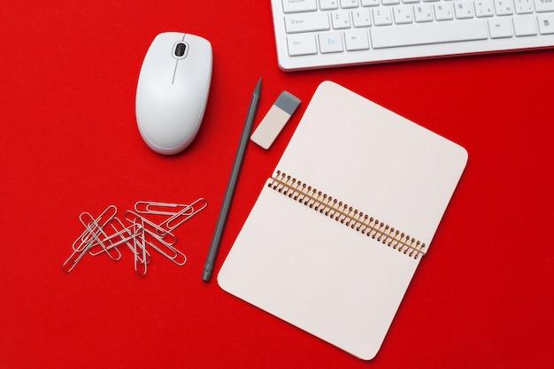 Красный офисный стол с канцелярскими и канцелярскими товарами