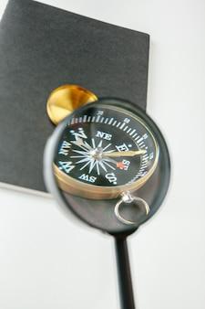 Золотой компас с черным блокнотом и ручкой крупным планом на столе