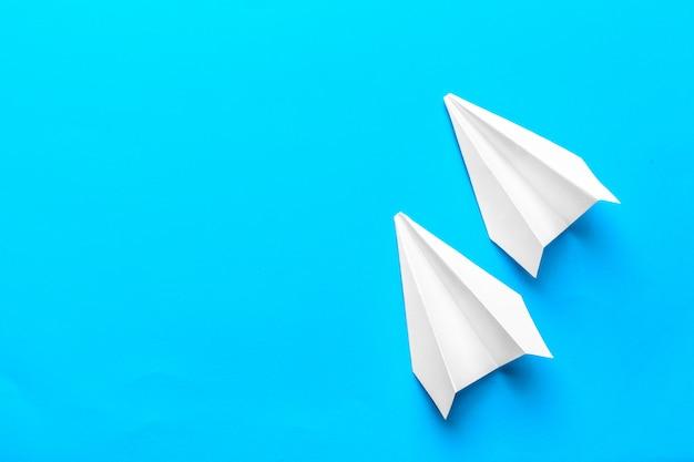 パステルブルーの色の背景に白い紙飛行機と白紙のフラットレイアウト