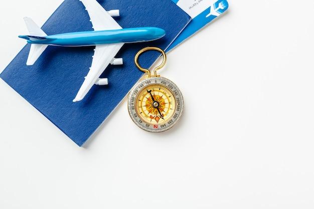 Время путешествовать. идея для туризма с авиабилетами и компасом на белом