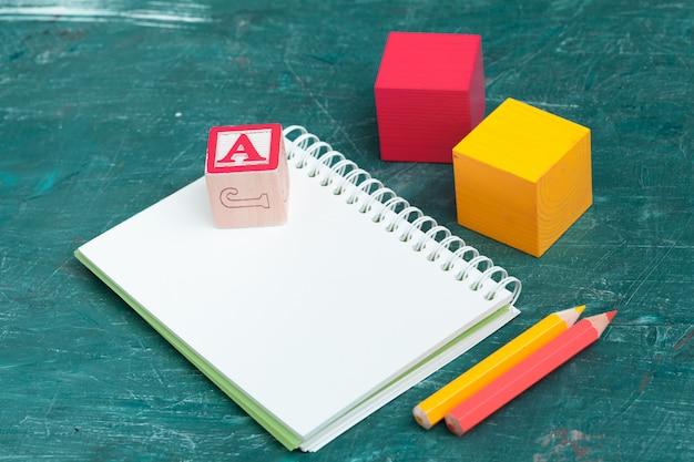 木製のテーブルと木製アルファベットブロックのメモ帳