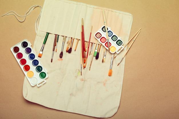 手作りのロールケースと水彩絵の具でプロの水彩画アーティストブラシのセットをクローズアップ