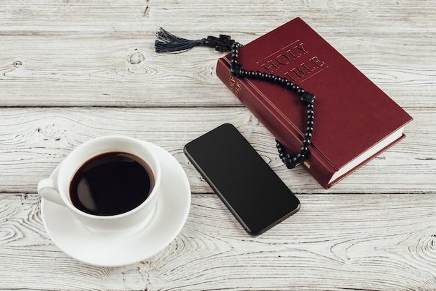 Библия и смартфон с чашкой черного кофе