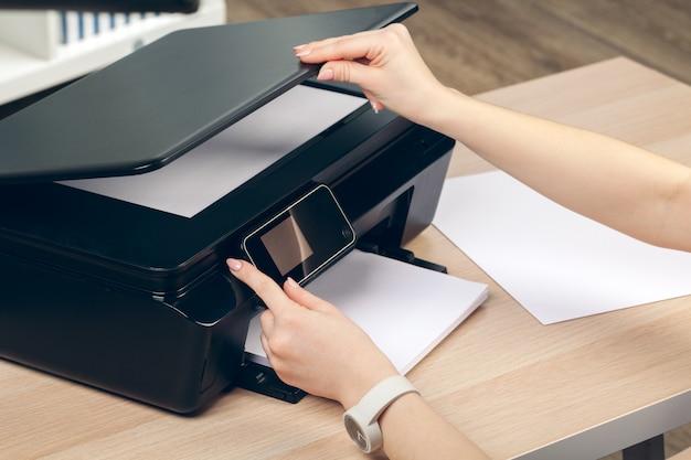 Женщина делает ксерокопию с использованием ксерокса в офисе