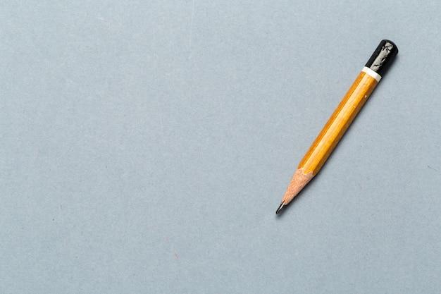 明るい灰色の背景に短いすり減った鉛筆の静物