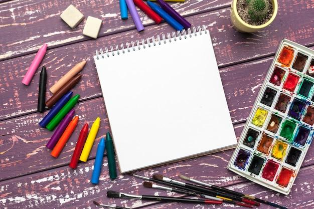 描画ツール、消耗品、アーティストの職場。水彩絵の具と木製の机の上の空白のメモ帳