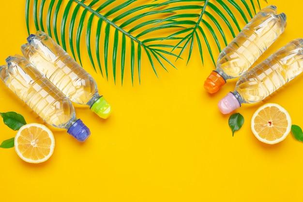 Листья тропика и вода бутылки на желтой предпосылке. детокс фруктовая вода.