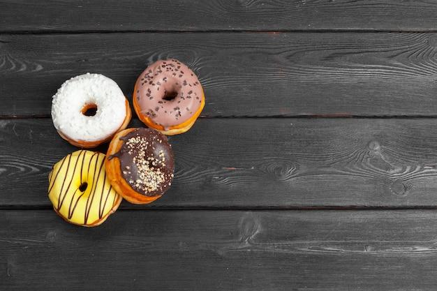 暗い黒い木製の表面の背景にカラフルな新鮮なドーナツ