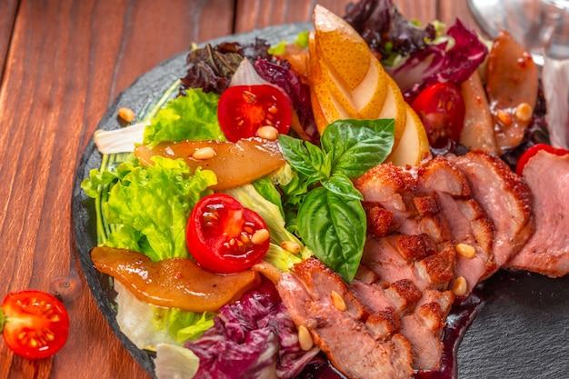 Вкусная нарезанная жареная утиная грудка с крупным планом салат из свежих овощей на тарелку.