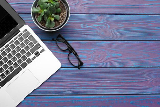 ラップトップ、メガネ、暗い青色の木製の背景平面図上の植物