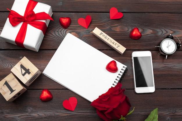 バレンタイン・デー。空の空白のノートブック、ギフトボックス、花