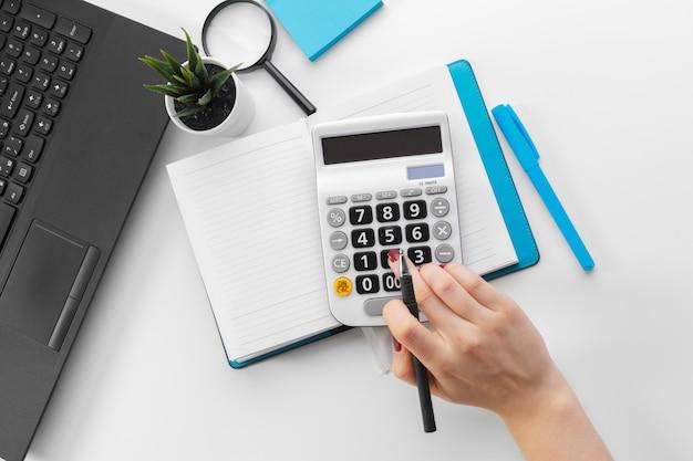 Бизнес женщина, работающая с рукой финансовых данных с помощью калькулятора