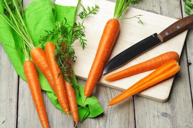 台所のまな板でスライスに健康なニンジンを刻んでください。