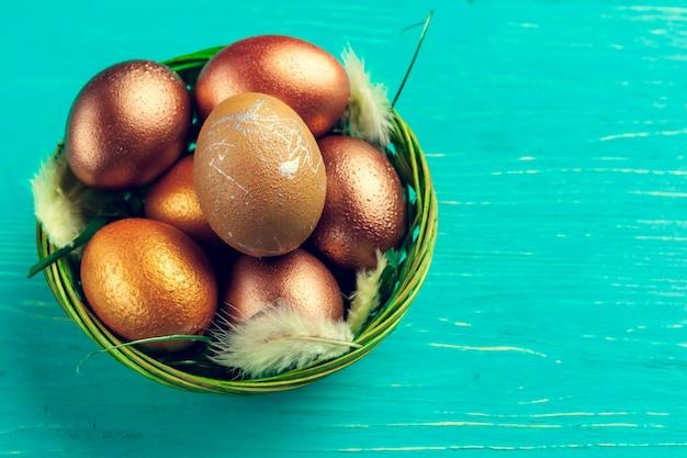 Золотые пасхальные яйца на деревянном столе