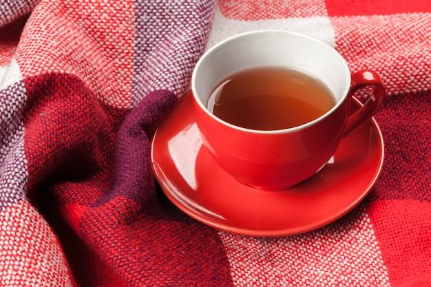暖かい冬のニットスカーフに身を包んだ熱いお茶のカップ