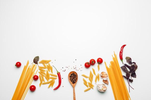 白い背景に、トップビューでパスタを調理するための食材のパスタスパゲッティ。