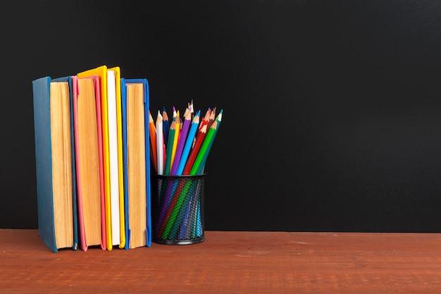 学校概念の背景に戻る。本と木製の机の上のリンゴと黒板
