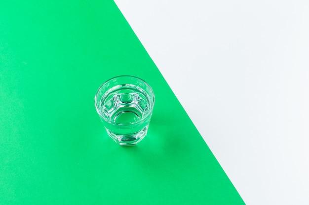 色の背景上の水のグラス