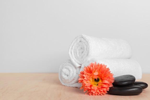 木製のテーブルの上に花ときれいな柔らかいタオル