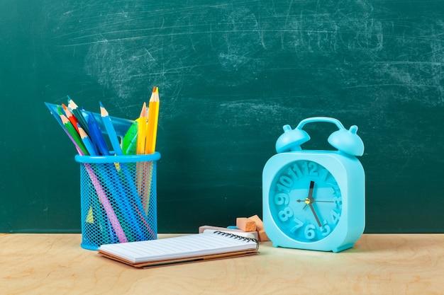学用品。筆記用具と目覚まし時計。概念を勉強する時間