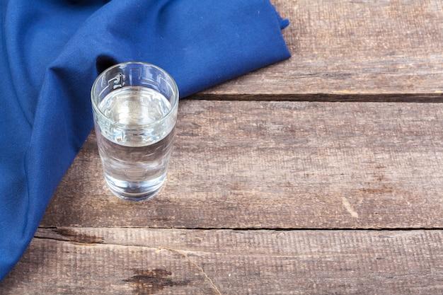 木製のテーブルの上に水のガラス