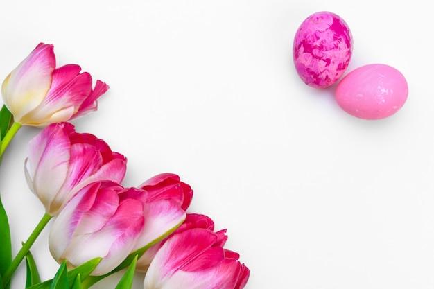 白い背景の上のチューリップの花とイースターエッグ