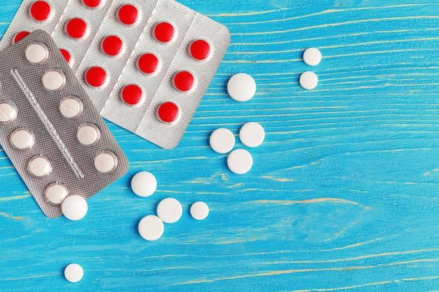 暗い青色の木製の背景に多くの異なる薬