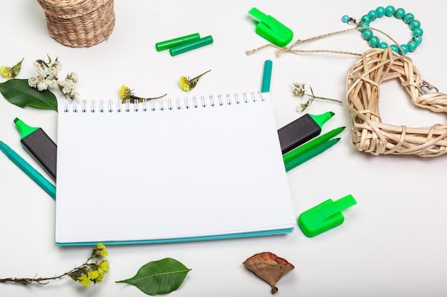 白いテーブルにスパイラルメモ帳の空白ページ。クレヨン鉛筆とペンフラットレイアウト。テーブルトップビューの空のスケッチブックページ。