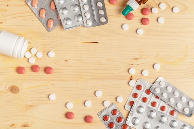 医療のカラフルな錠剤、カプセルまたは木製の背景に治療と健康管理のためのサプリメント