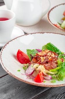 スライスしたたたきテンダーロインステーキと新鮮なグリーンサラダのクローズアップ