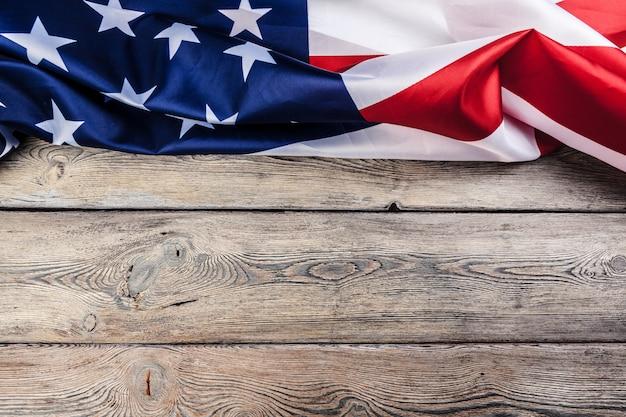 軽い木製のテーブルの背景にアメリカ国旗をコピースペースを閉じる