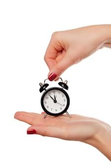 目覚まし時計を持っている女性の手
