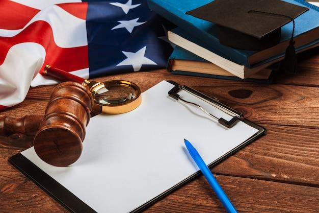 空白のクリップボードと木製テーブルの上の米国旗