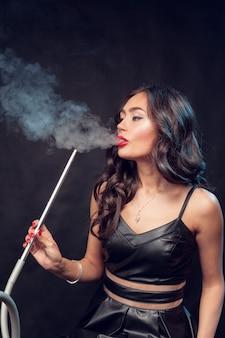 女性は水ギセルを吸う/黒のドレスで美しい魅力的な女性は水ギセルを吸う