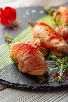 Спаржа, завернутая с кусочками куриного мяса, подается на темной тарелке