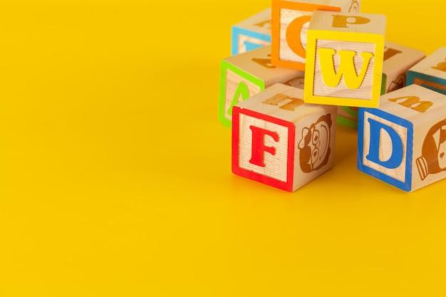 Красочные деревянные блоки с буквами на желтом фоне цвета