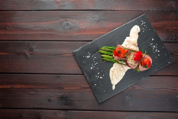 黒の食器、木製のテーブルにアスパラガスと子牛のメダリオン