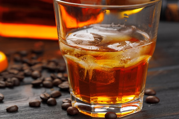 ウイスキーまたはリキュール、コーヒー豆、オレンジを木材にカットしました。季節の休日の概念。