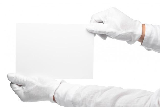 白紙のメモを持っている執事またはコンシェルジュの手。白で隔離される右側から伸ばした手で水平フォーマットアーム。