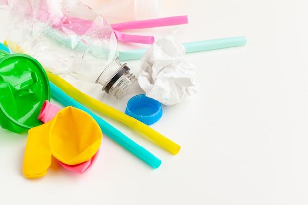 ゴミとカラフルな使い捨てストロー、カトラリーカップ、ボトルとプラスチック廃棄物危険生態学の概念