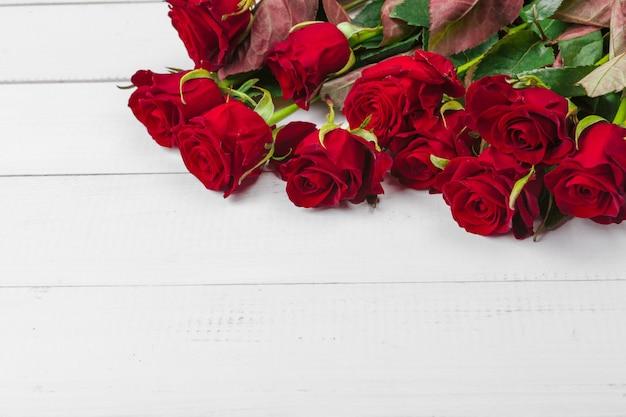 木製のテーブルに赤いバラとロマンチックな背景
