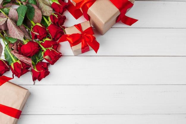 聖バレンタインデー。赤いバラと木製のテーブルのギフトボックス