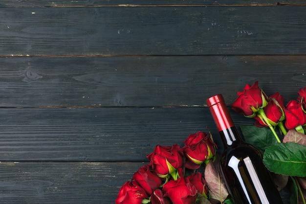 День святого валентина поздравительных открыток. цветки красной розы, вино и подарочная коробка на деревянном столе.