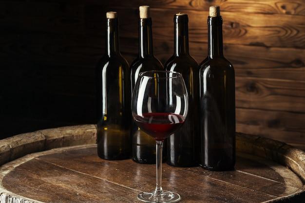 ボトルと木製樽で赤ワインのグラスは暗い木で撮影