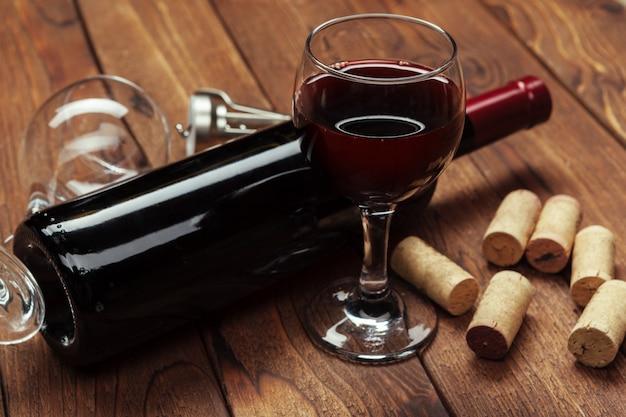赤ワインのボトル、ワイングラス、コルク栓抜き、木製テーブル