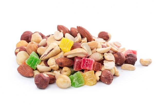 Куча жареных орехов и цукатов, изолированных на белом