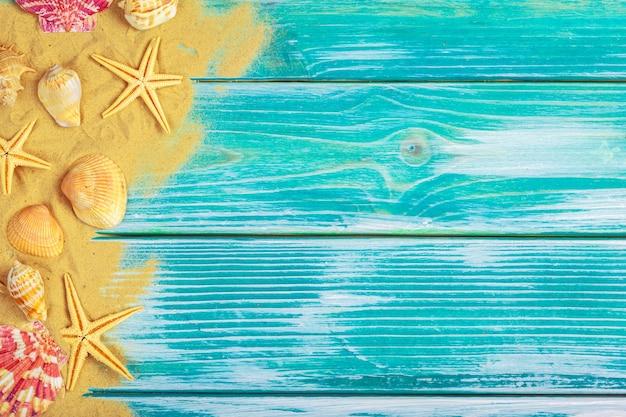 Морской песок и морские раковины на синем фоне деревянных