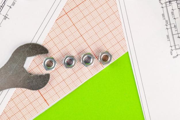 印刷された図面の背景に金属のボルトとナット